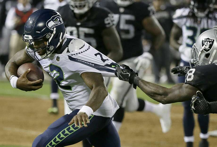 Seattle Seahawks quarterback Trevone Boykin (2) has his jersey pulled by Oakland Raiders defensive back Marcus McWilson during the first half of an NFL preseason football game in Oakland, Calif., Thursday, Aug. 31, 2017. (AP Photo/Eric Risberg) Photo: Eric Risberg/AP