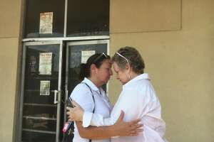 MANNA Executive Director Patricia Dornak and Terry Jeanes console each other after fire damaged the organization's thrift store Thursday in Houston.