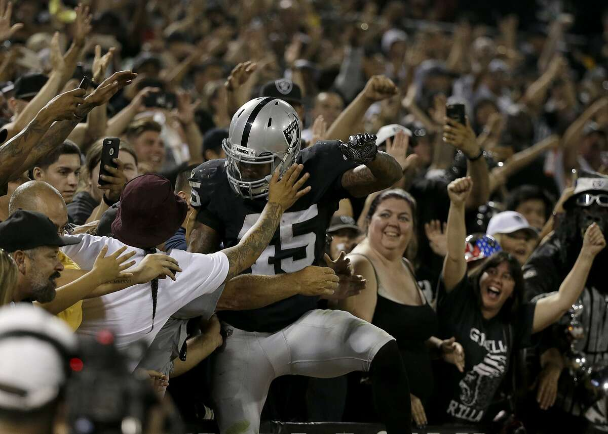 Oakland Raiders running back George Atkinson III (45) celebrates with fans during the second half of an NFL preseason football game against the Seattle Seahawks in Oakland, Calif., Thursday, Aug. 31, 2017. Atkinson had scored an apparent touchdown that called back on penalty. (AP Photo/Eric Risberg)