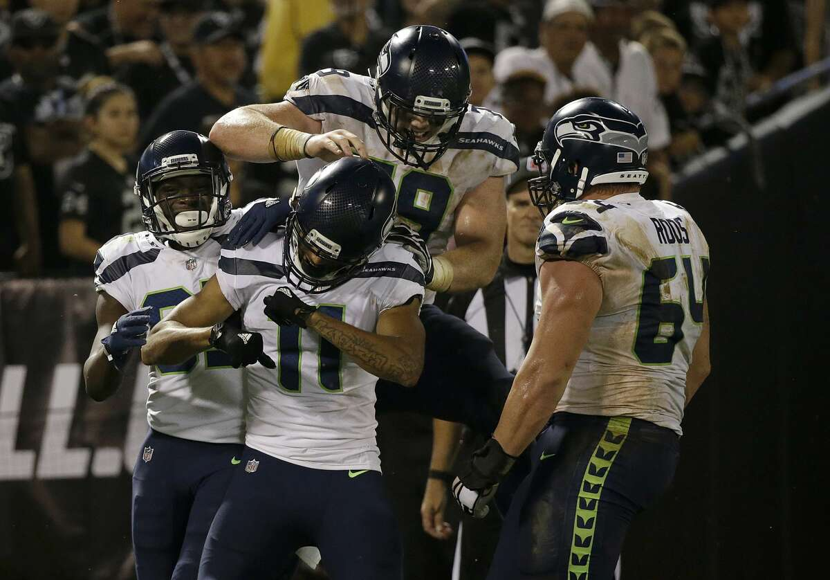 Seattle Seahawks wide receiver Kenny Lawler (11) celebrates with teammates after scoring a touchdown near the end of an NFL preseason football game against the Oakland Raiders in Oakland, Calif., Thursday, Aug. 31, 2017.