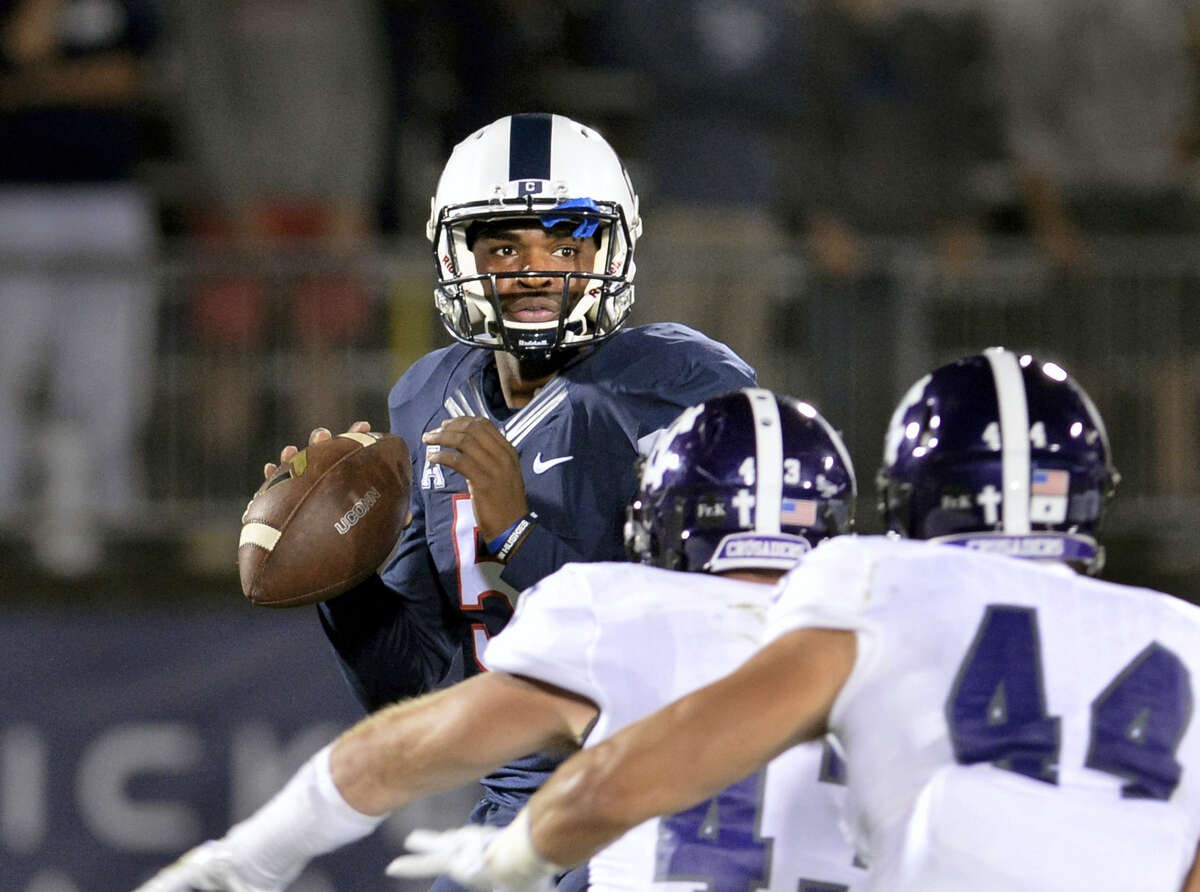 Connecticut quarterback David Pindell (5) looks for a receiver during the second quarter against Holy Cross during an NCAA college football game Thursday in East Hartford, Conn. UConn won 27-20.