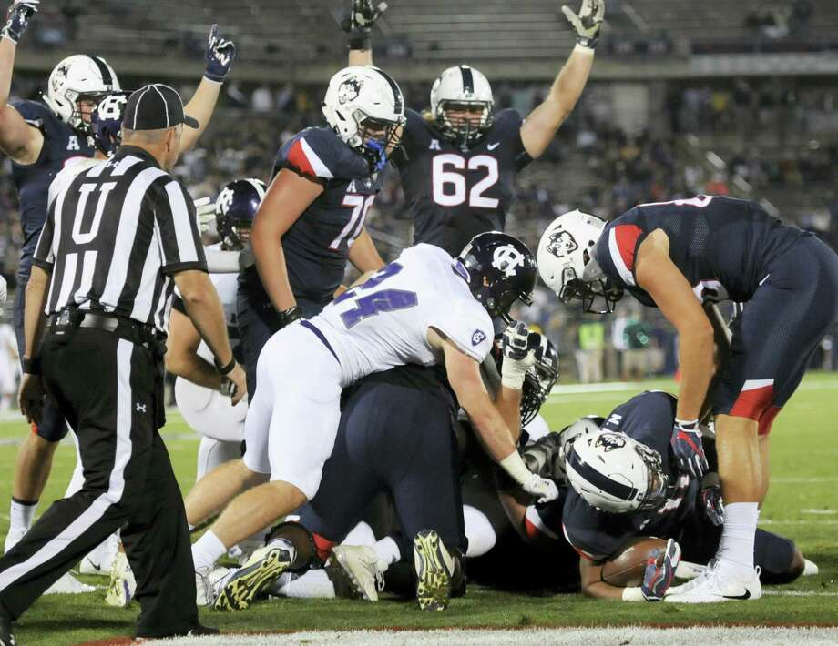 Connecticut running back Nate Hopkins (11) scores in the fourth quarter of an NCAA college football game against Holy Cross, Thursday in East Hartford, Conn. Photo: Stephen Dunn — The Associated Press / FR171426 AP