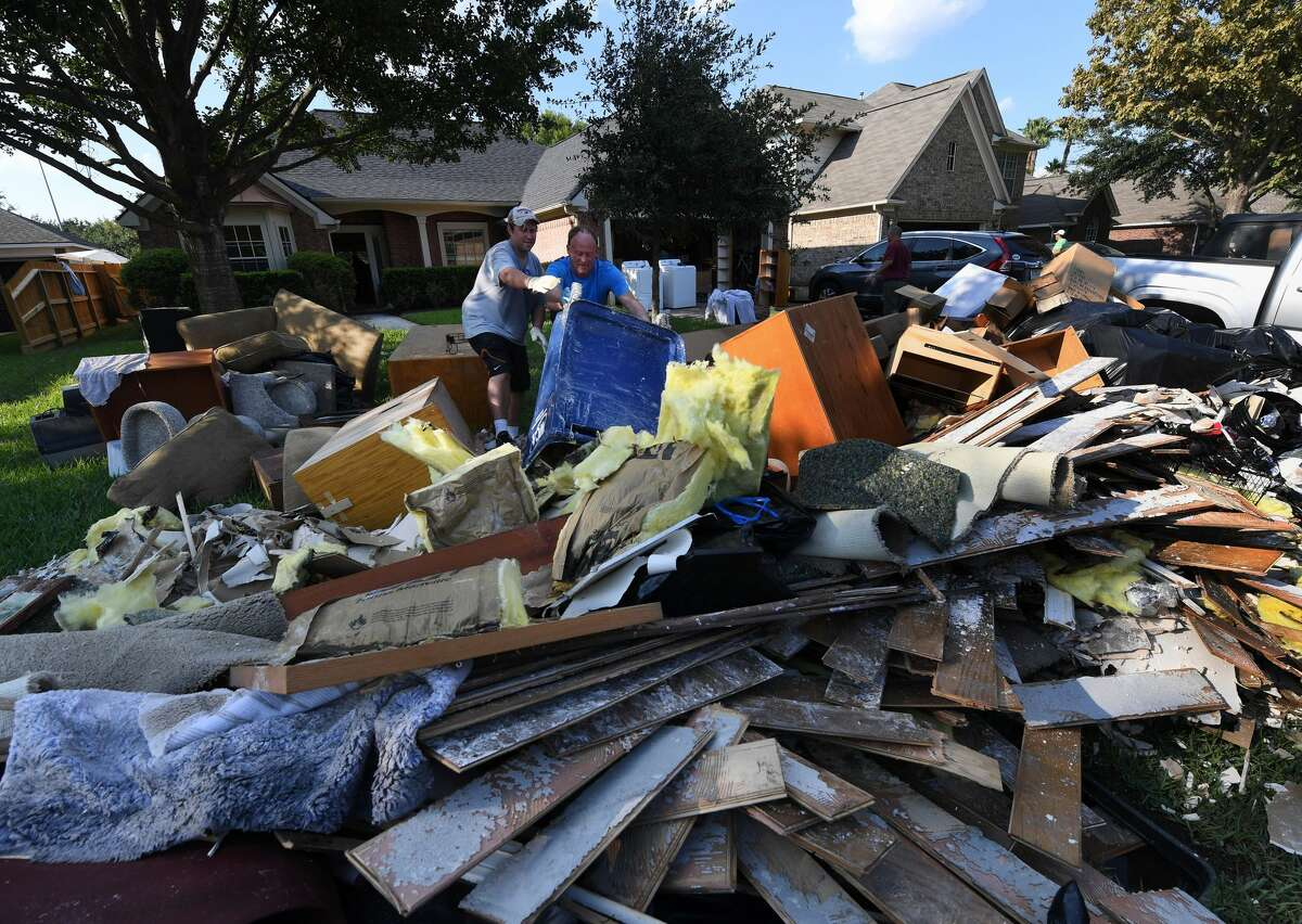 Members of the Olson family remove debris and damaged items from their father's home in the Twin Oaks Estate after Hurricane Harvey caused widespread flooding in Houston, Texas on August 31, 2017. In Houston, America's fourth-largest city, some of the 2.3 million residents got relief as the raging waters receded. But in several other towns in the Lone Star State doused by days of torrential rains since Harvey smashed into the US Gulf Coast almost a week ago as a Category Four hurricane, the situation was dire. / AFP PHOTO / MARK RALSTON (Photo credit should read MARK RALSTON/AFP/Getty Images)