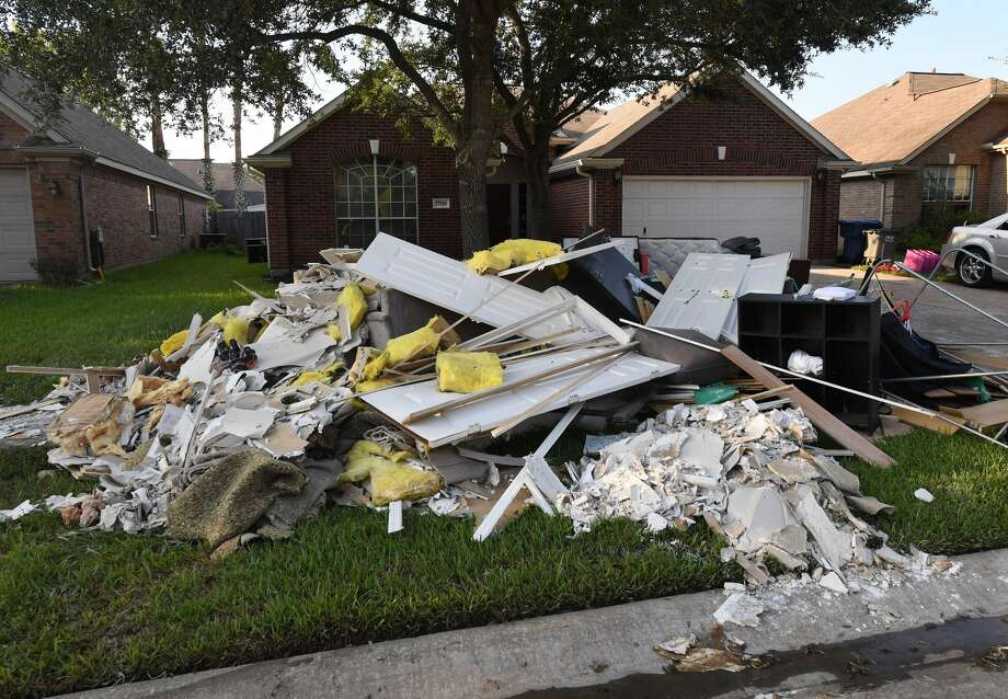 Debris and damaged items sit on the sidewalk after being removed from a home in the Twin Oaks Estate after Hurricane Harvey caused widespread flooding in Houston, Texas on August 31, 2017.   In Houston, America's fourth-largest city, some of the 2.3 million residents got relief as the raging waters receded. But in several other towns in the Lone Star State doused by days of torrential rains since Harvey smashed into the US Gulf Coast almost a week ago as a Category Four hurricane, the situation was dire.  / AFP PHOTO / MARK RALSTON        (Photo credit should read MARK RALSTON/AFP/Getty Images) Photo: MARK RALSTON/AFP/Getty Images