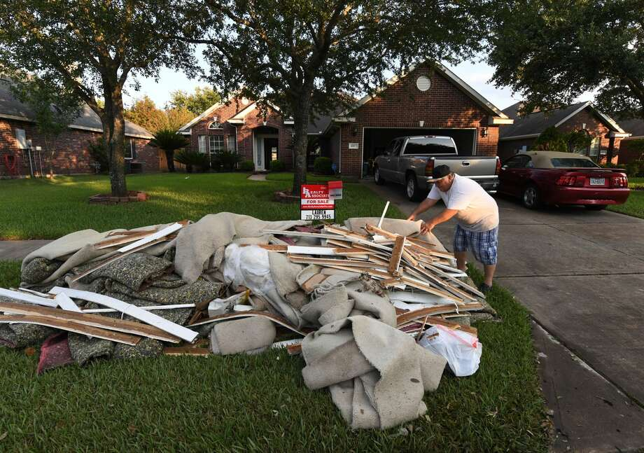 A member of the  Flores family whose home was flooded puts debris and damaged items sit on the sidewalk in the Twin Oaks Estate after Hurricane Harvey caused widespread flooding in Houston, Texas on August 31, 2017. In Houston, America's fourth-largest city, some of the 2.3 million residents got relief as the raging waters receded. But in several other towns in the Lone Star State doused by days of torrential rains since Harvey smashed into the US Gulf Coast almost a week ago as a Category Four hurricane, the situation was dire.  / AFP PHOTO / MARK RALSTON        (Photo credit should read MARK RALSTON/AFP/Getty Images) Photo: MARK RALSTON/AFP/Getty Images