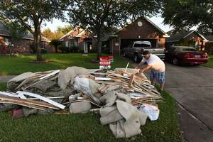 A member of the  Flores family whose home was flooded puts debris and damaged items sit on the sidewalk in the Twin Oaks Estate after Hurricane Harvey caused widespread flooding in Houston, Texas on August 31, 2017. In Houston, America's fourth-largest city, some of the 2.3 million residents got relief as the raging waters receded. But in several other towns in the Lone Star State doused by days of torrential rains since Harvey smashed into the US Gulf Coast almost a week ago as a Category Four hurricane, the situation was dire.  / AFP PHOTO / MARK RALSTON        (Photo credit should read MARK RALSTON/AFP/Getty Images)