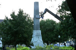 Crews work Friday September 1 , 2017 to remove the pedestal of the Confederate war memorial at Travis Park in San Antonio, Texas. The statue itself was removed earlier in the morning at about 2:00 a.m. and placed on a flatbed truck. San Antonio's City Council recently voted to have the memorial removed from the park.