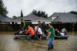 Rescuers bring a group of people down Addicks Satsuma Road as they help them evacuate as Addicks Reservoir nears capacity Tuesday, Aug. 29, 2017 in Houston. ( Michael Ciaglo / Houston Chronicle)