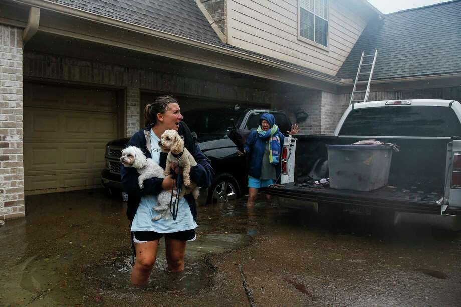 A woman carries her dogs as she is evacuated from the Twin Lakes neighborhood with her family as Addicks Reservoir nears capacity due to near constant rain from Tropical Storm Harvey Tuesday, Aug. 29, 2017 in Houston. ( Michael Ciaglo / Houston Chronicle) Photo: Michael Ciaglo, Staff / Michael Ciaglo