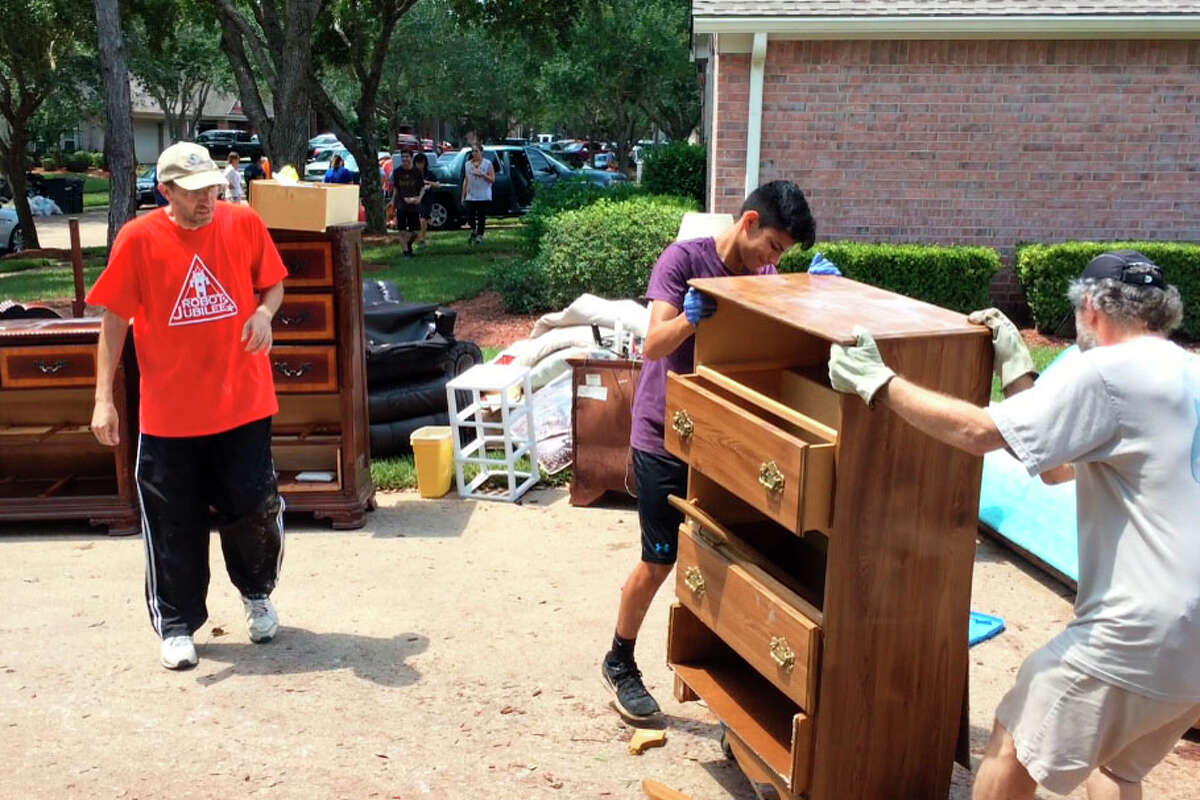 Joey Barcio watches as volunteers remove furniture from his parent's house after Hurricane Harvey Thursday Aug. 31.