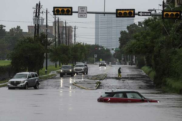 A car sits stranded in high water at Studemont Drive and Allen Parkway as Buffalo Bayou overflows its banks as Tropical Storm Harvey continued to dump rain across the region Tuesday in Houston.
