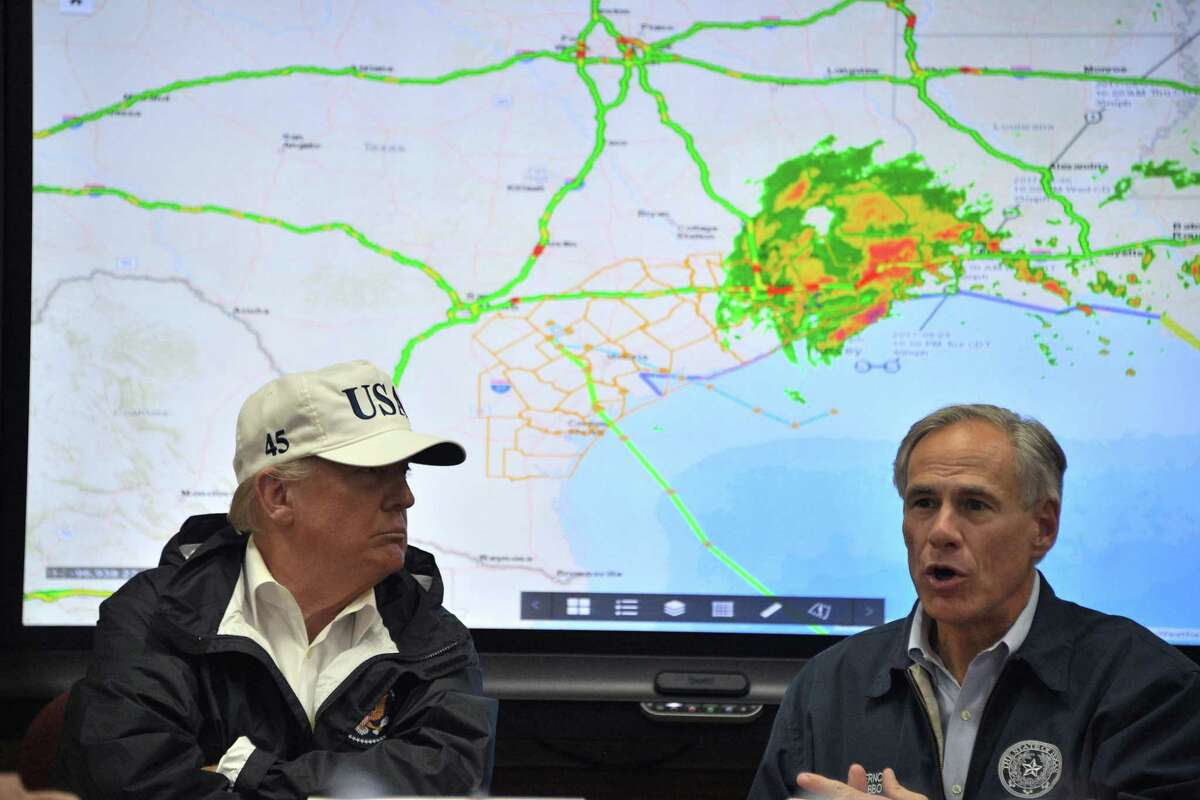 Texas Governor Greg Abbott speaks next to President Donald Trump at the Texas Department of Public Safety Emergency Operations Center in Corpus Christi, Texas on Tuesday. Both have dabbled in climate change denial. Perhaps Harvey will change that.