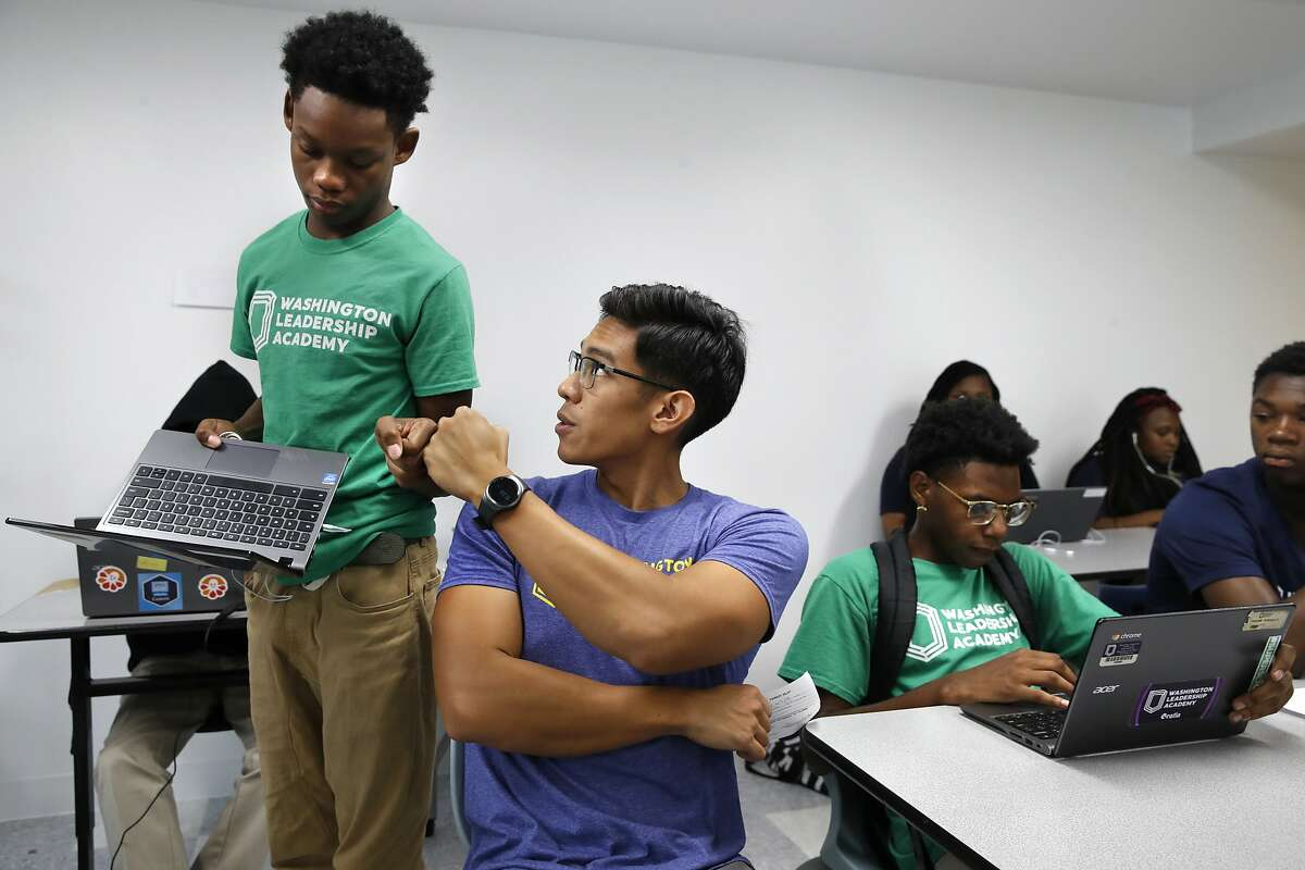 """Tamar Champion, 14, left, gets a """"fist bump"""" from teacher Enrique Ramos, as he shows his teacher his results after taking a diagnostic test using special software in his literacy studio class at the Washington Leadership Academy, Wednesday, Aug. 23, 2017, in Washington. The system diagnoses students' proficiency levels in real time, part of """"personalized learning."""" This approach uses software, data and constant monitoring of student progress to adapt teaching to each child's strengths, weaknesses, interests and goals and enable them to master topics at their own speed. (AP Photo/Jacquelyn Martin)"""