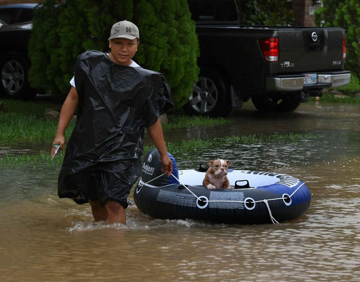 John Tuan returns to rescue his dog who was left in his flooded house in the Clodine district after Hurricane Harvey caused heavy flooding in Houston, Texas on August 29, 2017. Floodwaters have breached a levee south of the city of Houston, officials said Tuesday, urging residents to leave the area immediately. / AFP PHOTO / MARK RALSTON (Photo credit should read MARK RALSTON/AFP/Getty Images)