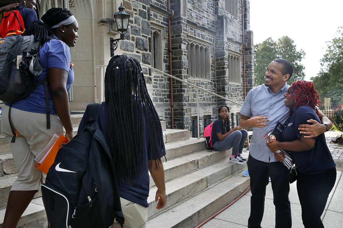 """Anthony Guyton, dean of students at Washington Leadership Academy, hugs Indiae Gill, right, as she and other students arrive in the morning at the school in Washington, Wednesday, Aug. 23, 2017. The school specializes in taking a personalized approach to community and learning. The school utilizes """"personalized learning,"""" an approach that uses software, data and constant monitoring of student progress to adapt teaching to each child's strengths, weaknesses, interests and goals and enable them to master topics at their own speed. (AP Photo/Jacquelyn Martin)"""