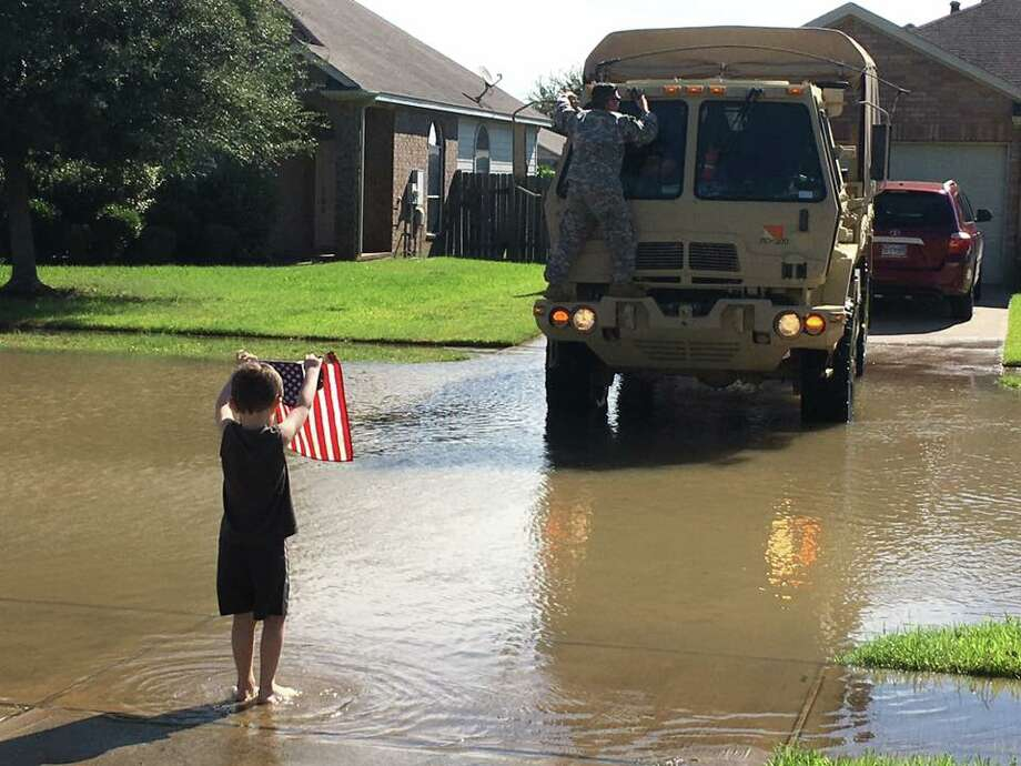 John Wesley Claburn IV, or J.W., is seen welcoming the National Guard to his Richmond neighborhood with an American flag on Aug. 31. Photo: Emily Claburn/Facebook