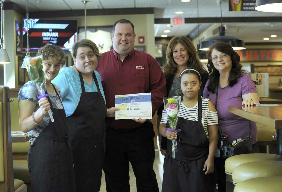 Ability Beyond staff members and clients present Joe Moir, general manager of 99 Restaurant in Danbury, center, with  roses and a certificate of appreciation Thursday, August 31, 2017. From left are Ability Beyond clients who work at 99, Rachel Dennerlien, Jamie Bucur and Veronica S, and Karen Samperi, Ability day program manager and Dorothy Schaffer, program facilitator. Photo: Carol Kaliff / Hearst Connecticut Media / The News-Times