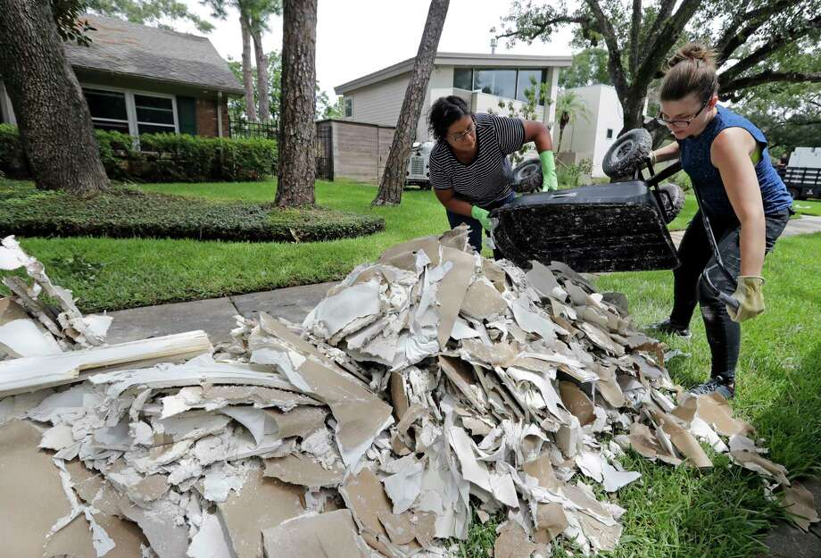 Adriana Perez, left, and Clair Hummel help remove waterlogged drywall from the home of a friend days after Tropical Storm Harvey.  Photo: David J. Phillip, Associated Press / Copyright 2017 The Associated Press. All rights reserved.