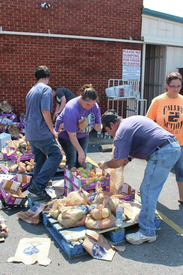 Volunteers prepare food bags to distribute to people in a line of cars outside of Covenant for Christ Resale Shop in Cleveland. The food donations are expected to continue through the next several days. Photo: Vanesa Brashier