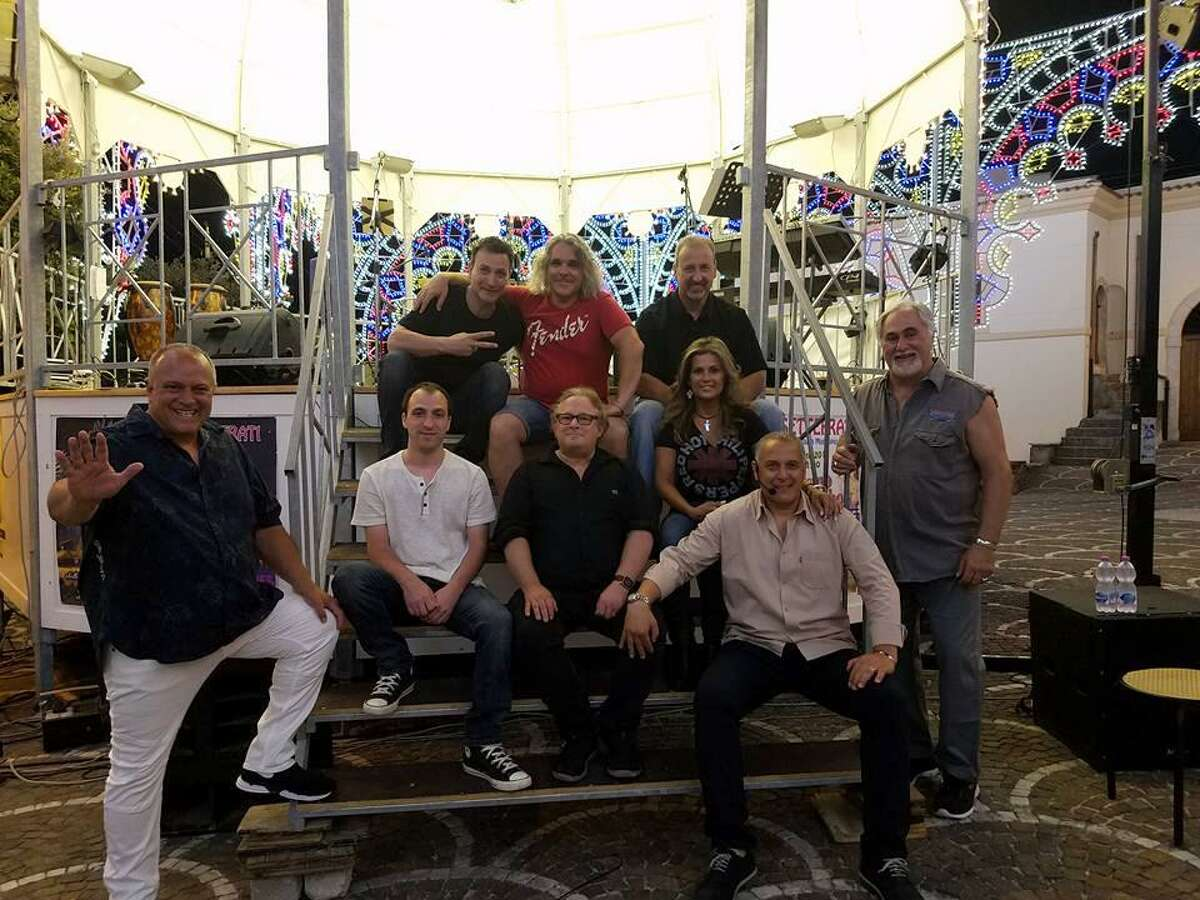 A group of Stamford musicians formed a band, Eight-Track Playback, to perform in Stamford?'s Italian sister city, Settefrati, during a festival in August. The members are, seated in top row from left, Mario Socci, Nick Casinelli and Mike Giordano; seated in second row, from left, Anthony Socci, Allan Tepper and Rosie Burgos; standing, left, Gerard Diacri; and standing, right, Milo Fuscaldo. A citizen of Settefrati, seated, bottom row, poses with them.