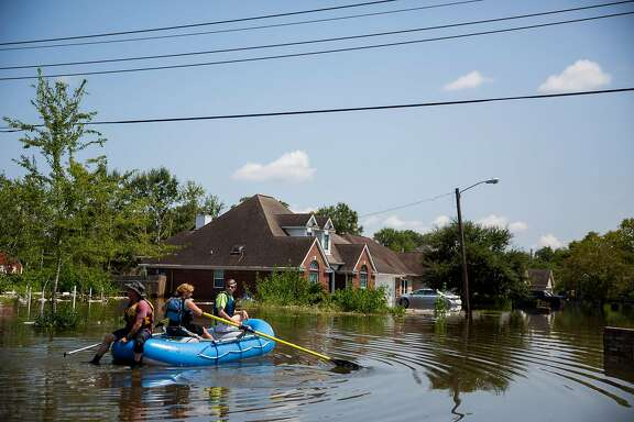 People ride into a flooded neighborhood in Beaumont, Texas, Sept. 1, 2017. A week after Harvey began battering southeast Texas, residents in some places returned home and began the long, hard slog toward recovery, while other areas remained very much in the midst of a crisis on Friday. (Eric Thayer/The New York Times)