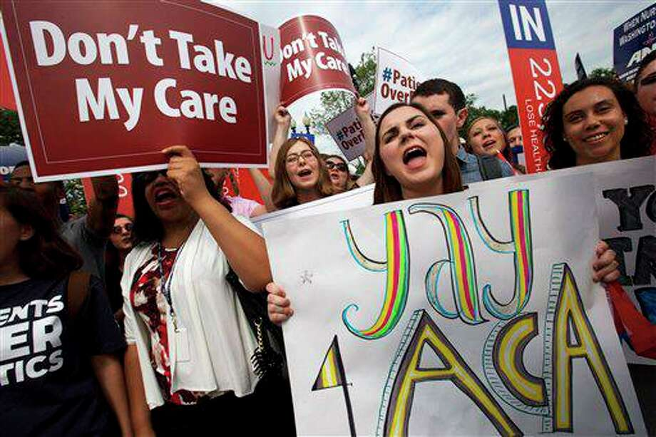 """Jessica Ellis, right, holds a sign that says """"yay 4 ACA,"""" as she and other supporters of the Affordable Care Act react with cheers as the opinion for health care is reported outside of the Supreme Court in Washington, June 25, 2015, in Washington. A reader is not pleased with the way ACA has impacted the affordability of healthcare. Photo: Jacquelyn Martin /AP / AP"""