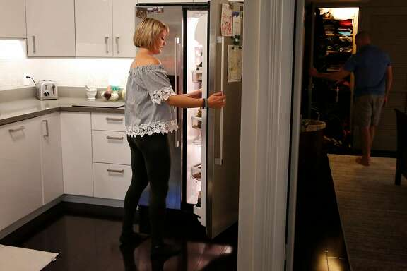 Corinna Heyn-Jones searches through the refrigerator for muffin makings as her partner Chad Dussiaume roots through his closet for a speaker in the apartment they are short-term leasing through Homesuite August 31, 2017 in San Francisco, Calif. The couple are traveling nurses and are currently working out of San Francisco.