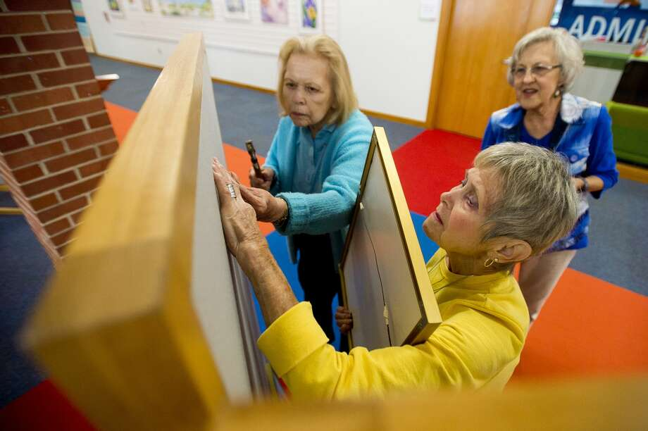 Barb Zimmerman of Midland, center, Arlene Thompson of Midland, left, and Margaret Heitzig of Midland, right, work to hang a watercolor painting on the wall for an exhibit on Friday, September 1, 2017 at the Grace A. Dow Memorial Library. Nearly 70 works of art by members of the Midland Water Media Society are on display through September 30. Photo: (Katy Kildee/kkildee@mdn.net)