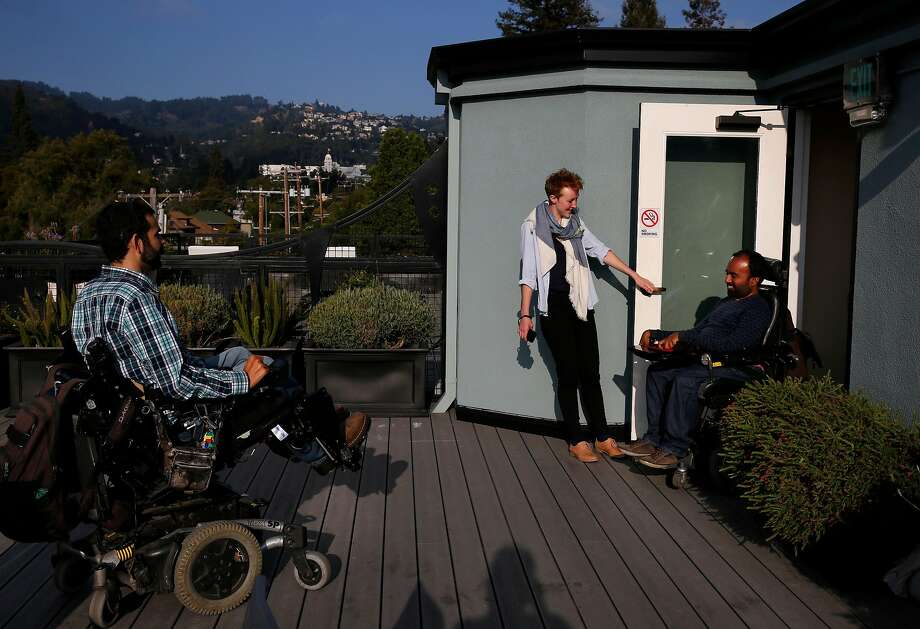 Alex Ghenis, left, shows Accomable co-founder and CEO Srin Madipalli, right, the roof as data scientist Vicky Clayton holds the door during a tour for the Chronicle August 23, 2017 in Berkeley, Calif. Ghenis is putting his apartment up on Accomable. Photo: Leah Millis, The Chronicle