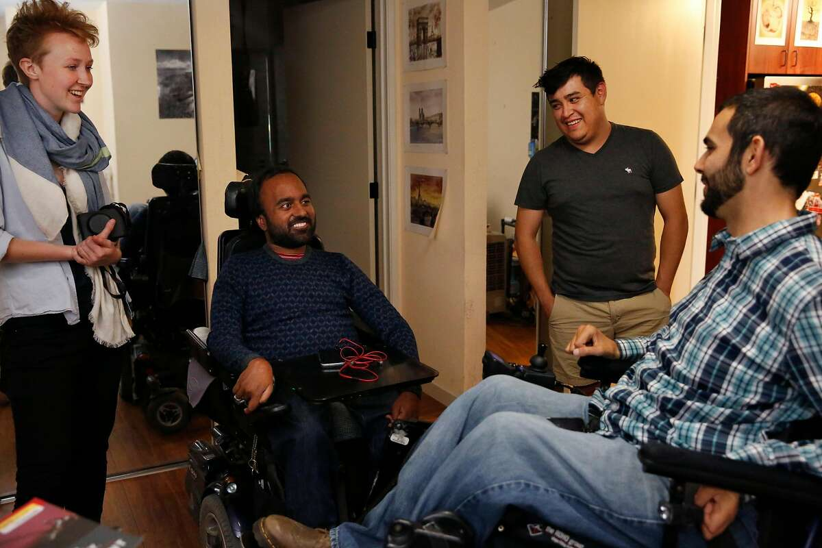 Alex Ghenis, right, chats with Accomable co-founder and CEO Srin Madipalli, second from left, data scientist Vicky Clayton, far left, and roommate and care taker Daniel Villalobos in Ghenis' room during a tour for the Chronicle August 23, 2017 in Berkeley, Calif. Ghenis is putting his apartment up on Accomable.