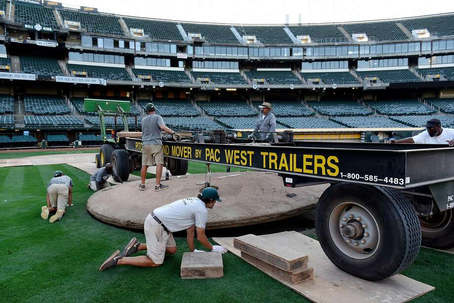 Groundskeepers at the Oakland Coliseum, the last dual-sport stadium in the country, use a lift trailer to hoist the pitching mound so it can be removed as they convert the baseball diamond into a football field. Photo: Michael Short, Special To The Chronicle
