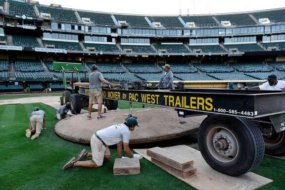 Groundskeeper members use a lift trailer to hoist the pitching mound so it can be moved off the field, as work to convert the field from baseball to football takes place at the Oakland Coliseum in Oakland, Calif., on Sunday August 27, 2017.