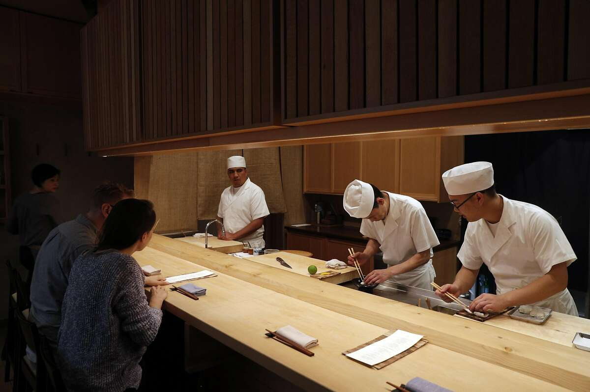 Customers watch sushi chefs (l-r) Eddie Trujillo, Alex Kim, and Sam Chen at Ijji sushi restaurant in San Francisco, Calif., on Wednesday, July 26, 2017. Ijji features an Omakase, or chef tasting service.