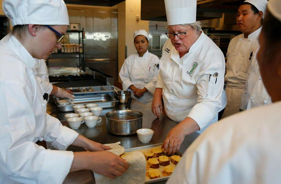 Chef instructor Jennifer Rudd (right) talks with students K. Marsh (left), Karen Yu, Sai Lu and Teodora De Lunas Aquino about recently baked bread with melted cheese during a culinary arts basic training class at the Chinatown/North Beach Center of the City College of San Francisco. Photo: Leah Millis, The Chronicle