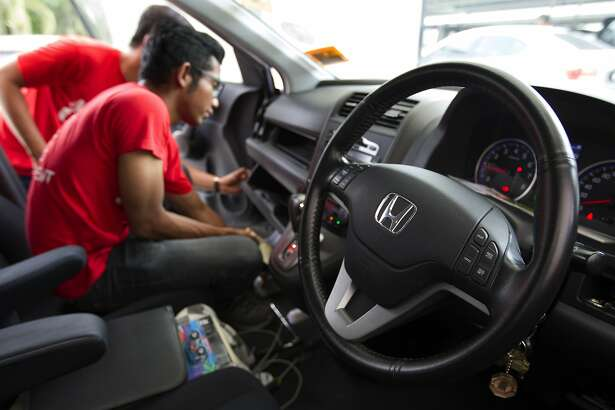 FILE - In this Sunday, Nov. 20, 2016, file photo, a Honda technician works on an airbag during a free airbag replacement event in Kuala Lumpur, Malaysia. Honda and some of the people suing the company over faulty Takata air bag inflators have agreed to a $605 million settlement. It covers owners of 16.5 million Honda vehicles. Honda gets credit for $121 million it spent on rental cars for customers who had to wait for parts. That leaves $484 million to reimburse owners for expenses, attorney fees and administrative costs. (AP Photo/Lim Huey Teng, File)