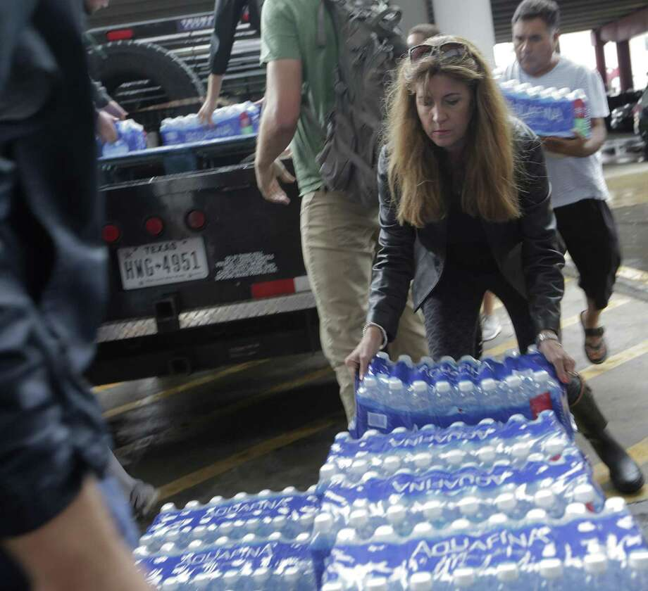 Merrill Eliff drops off donated water  at the George R. Brown Convention Center in Houston as Tropical Storm Harvey inches its way through the area on Tuesday. This is commendable charity, but that guy selling water at a slight markup is not a price gouger. Photo: Elizabeth Conley /Houston Chronicle / © 2017 Houston Chronicle