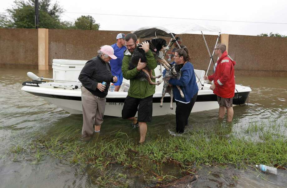 Shelly Jones gets help carrying her dogs out of the boat belonging to Josh Mtanyos with the Cajun Navy after their rescue Tuesday just north of FM 1960. Photo: Karen Warren, Staff Photographer / @ 2017 Houston Chronicle