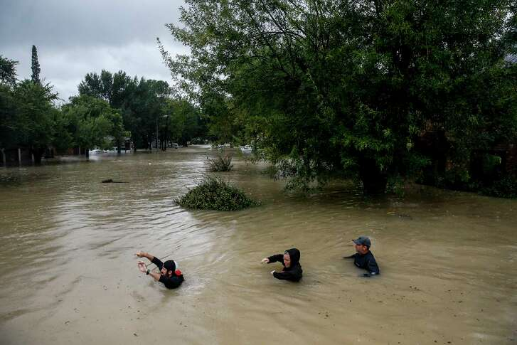 Residents make their way along Pine Cliff Drive near the Addicks Reservoir during flooding from Hurricane Harvey. The dual punch of Harvey and Irma took more than 100 lives.