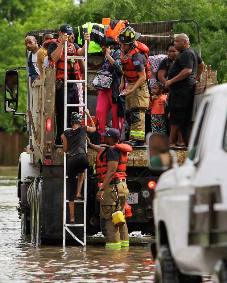 Firefighters help a woman onto a rescue dump truck during flooding Monday in the Greenspoint area. Both official and unofficial rescuers were alerted to stranded residents via social media during the storm. Photo: Michael Ciaglo, Staff / © 2016  Houston Chronicle