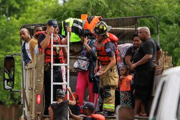 Firefighters help a woman onto a rescue dump truck during flooding Monday in the Greenspoint area. Both official and unofficial rescuers were alerted to stranded residents via social media during the storm.