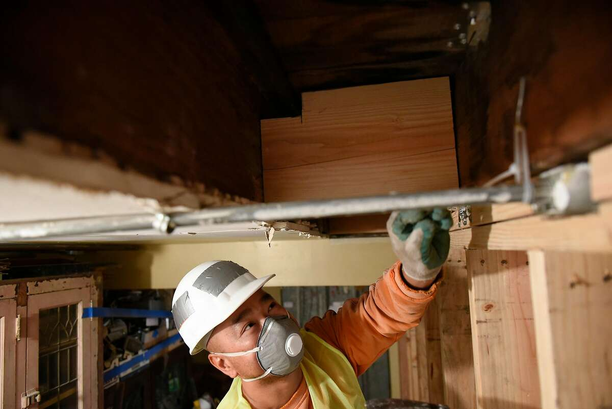 Construction worker Yuen Liang attaches angle straps to the top plate of a floor joist as SGDM contractors retrofit a mixed residential and commercial building in San Francisco, Calif., on Thursday August 31, 2017. Property owners in San Francisco are scrambling to retrofit their buildings as a new deadline looms for bringing buildings into compliance with the earthquake safety focused