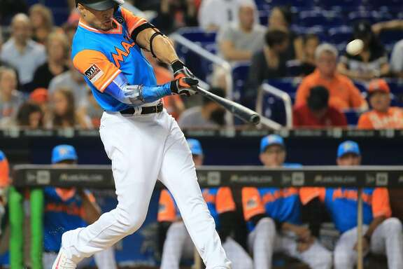 Miami Marlins right fielder Giancarlo Stanton (27) hits a home run and brings in second baseman Dee Gordon (9) to score in the first inning as the Marlins host the San Diego Padres on Friday, Aug. 25, 2017 at Marlins Park in Miami, Fla. (Al Diaz/Miami Herald/TNS)