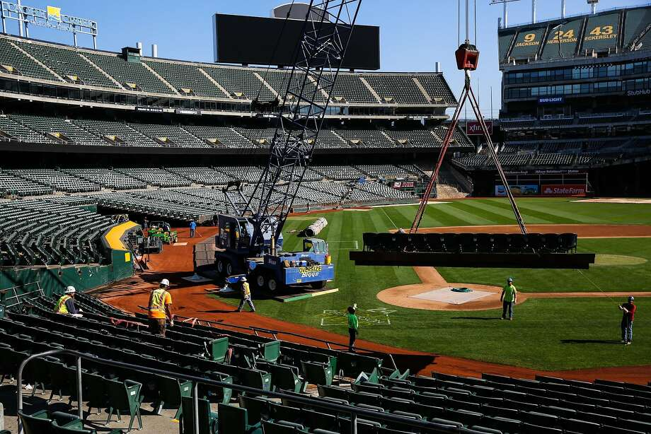 Workers move seats around to convert the Oakland Coliseum field from baseball to football. Photo: Gabrielle Lurie, The Chronicle