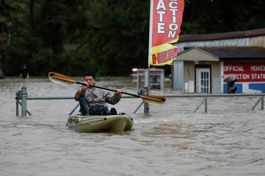 A rescuer in a kayak checks a flooded neighborhood in Houston.  Photo: Karen Warren, Staff Photographer / @ 2017 Houston Chronicle