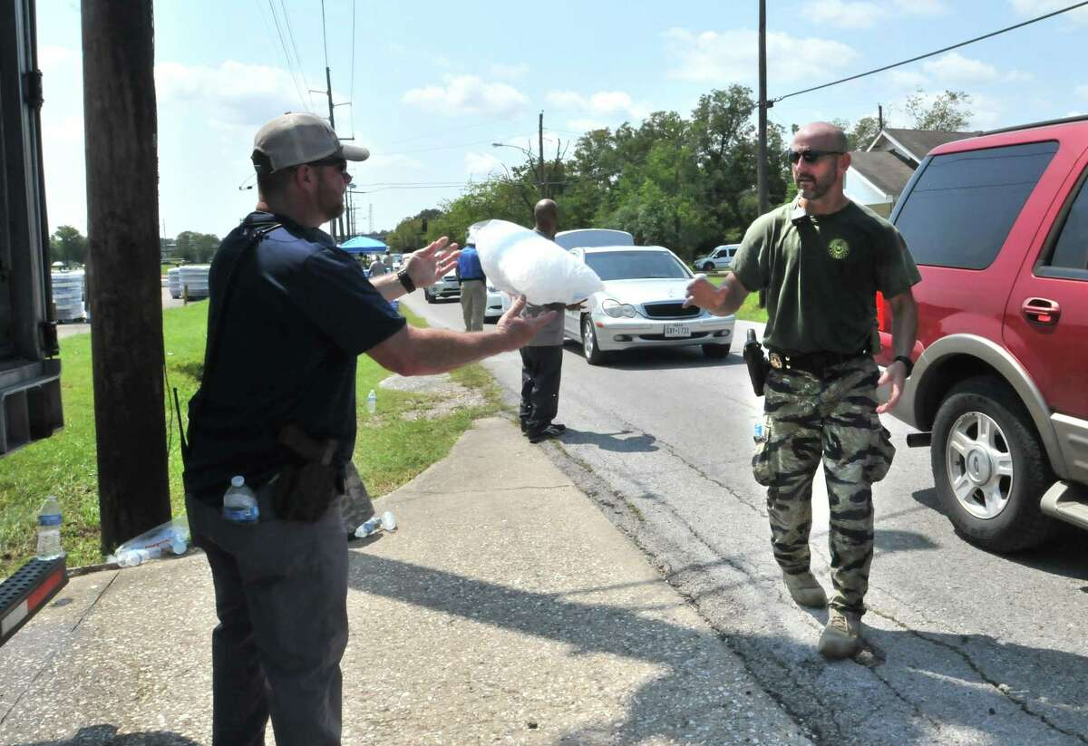 Beaumont police officer James Powell is tossed a bag of ice to load into cars as motorists drive through a water distribution line set up by city workers, police and Texas National Guard members behind Babe Zaharias Memorial Stadium on Friday in Beaumont. (Mike Tobias/The Enterprise)