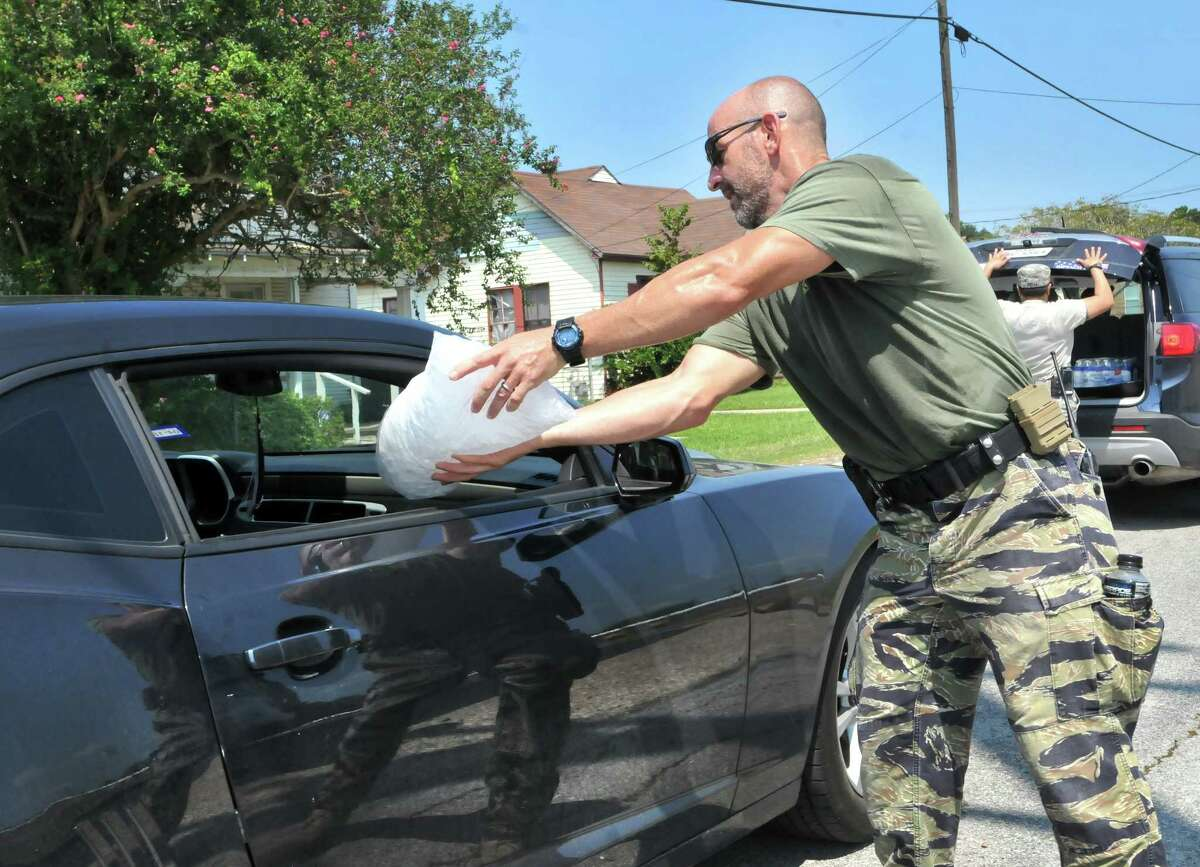 Beaumont police officer James Powell loads a bag of ice into a car as motorists drive through a water distribution line set up by city workers, police and Texas National Guard members behind Babe Zaharias Memorial Stadium on Friday in Beaumont. (Mike Tobias/The Enterprise)