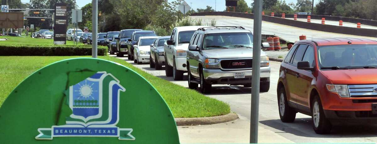 Motorists drive through a water distribution line set up by City of Beaumont workers, Beaumont police and Texas National Guard members behind Babe Zaharias Memorial Stadium on Friday in Beaumont. (Mike Tobias/The Enterprise)