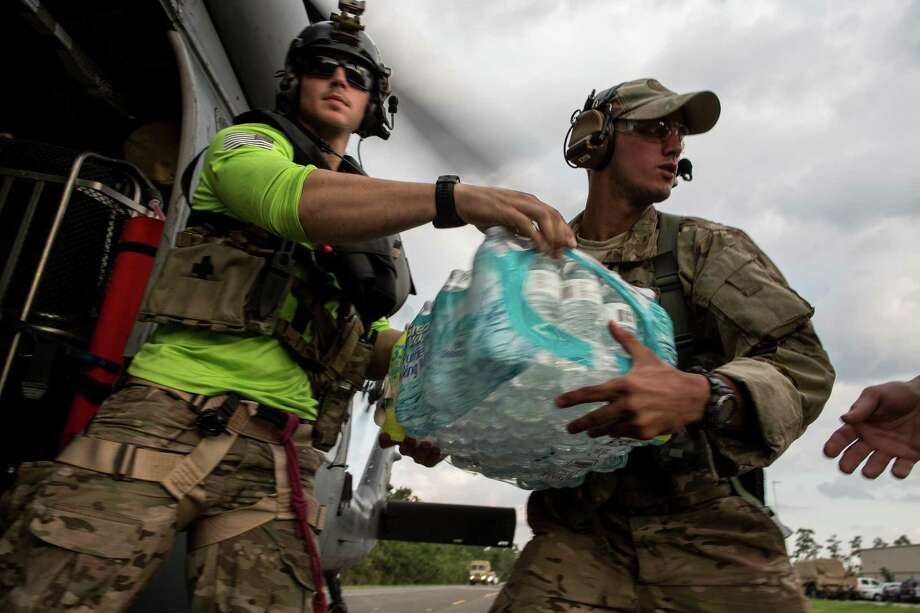 Senior Airman Adam Secore, a pararescue team member based at Moody AFB, hands off bottled water at a military staging area in Beaumont. Photo: Christoper Lee /New York Times / NYTNS