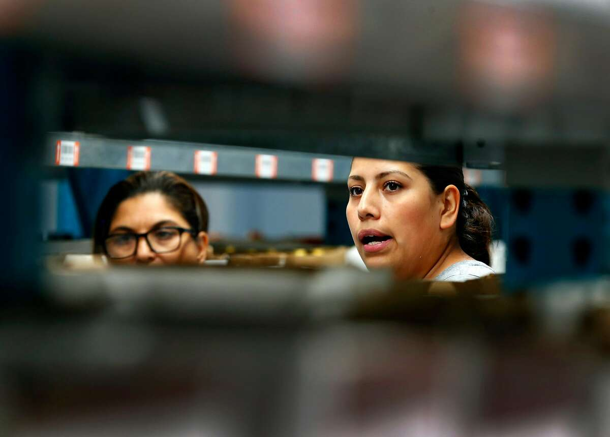 Luz Martinez (left) and Maria Briones restock shelves at the Wine Direct fulfillment and distribution center in American Canyon, Calif. on Tuesday, Aug. 29, 2017.