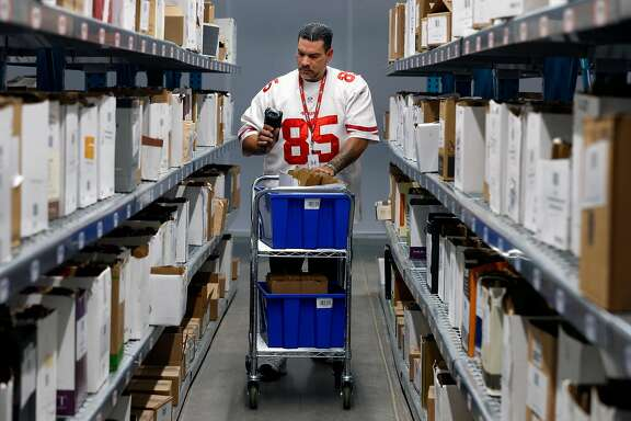William Brewer uses a handheld scanner to locate bottles of wine to be shipped to customers at the Wine Direct fulfillment and distribution center in American Canyon, Calif. on Tuesday, Aug. 29, 2017.